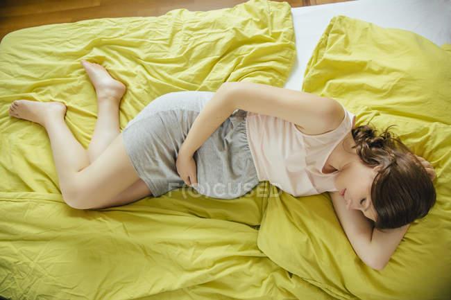Schwangere Frau auf Bett zu Hause während des Tages schlafen — Stockfoto