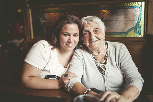 Portrait of smiling senior woman and her granddaughter sitting head to head in a restaurant — Stock Photo