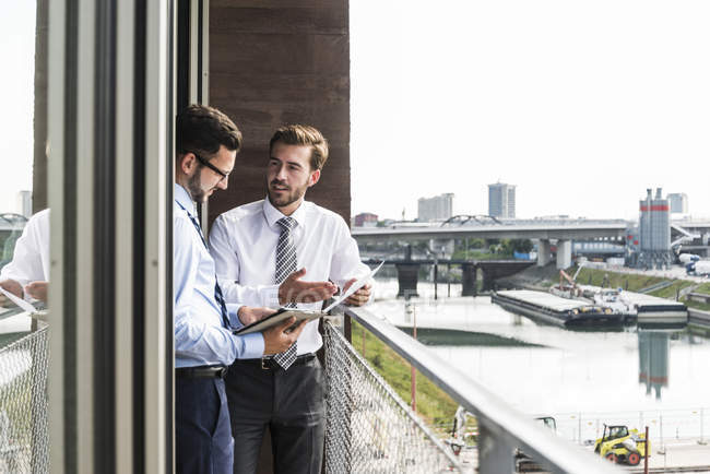 Two young businessmen with documents and digital tablet discussing on balcony — Stock Photo