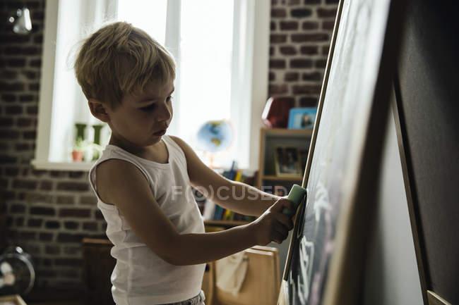Маленький хлопчик, спираючись на борту крейди у дитячу кімнату — стокове фото