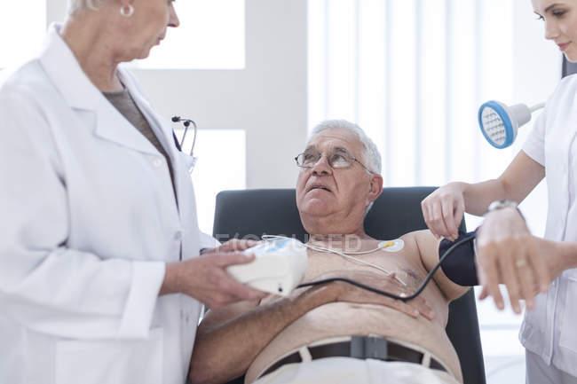 Senior man doing chek up in hospital, looking worried — Stock Photo