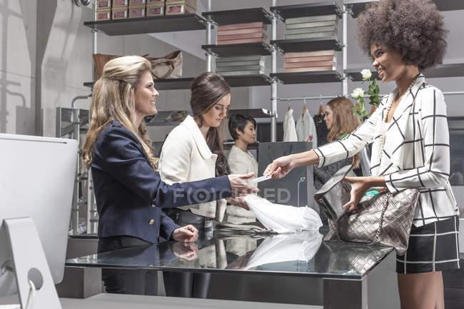Femme payant avec carte dans une boutique de luxe — Photo de stock