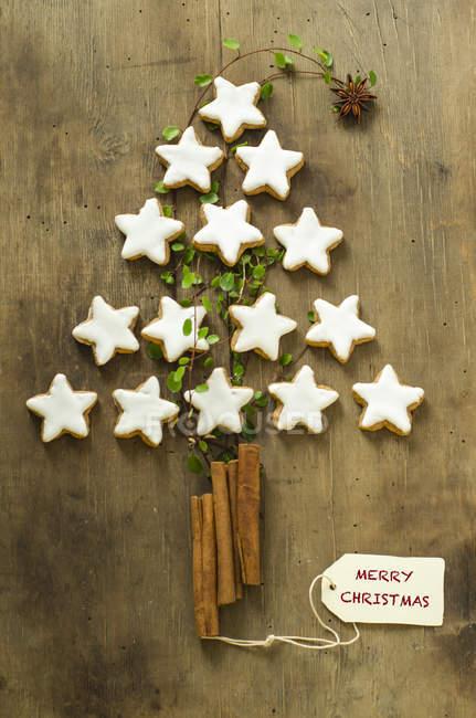 Weihnachtsbaumform aus Zimtsternen und Stäbchen auf Holz — Stockfoto