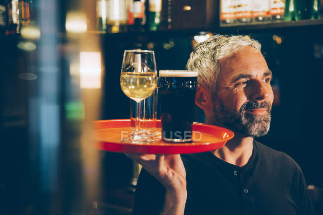 Kellner halten Traywith Getränke in einem irischen pub — Stockfoto