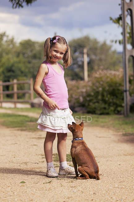 Портрет улыбающейся маленькой девочки со своей собакой — стоковое фото