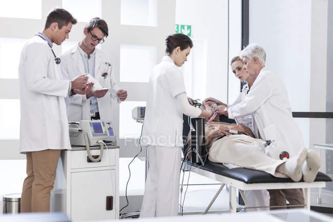 Personal del hospital ayudar a paciente en emergencia - foto de stock