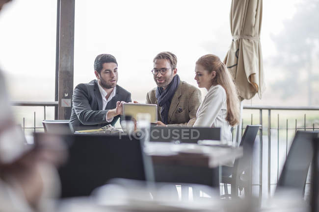 Three people having a meeting at restaurant — Stock Photo