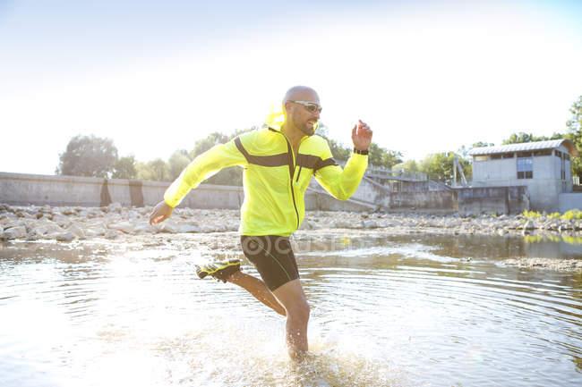 Homem em roupas esportivas, correndo na água — Fotografia de Stock