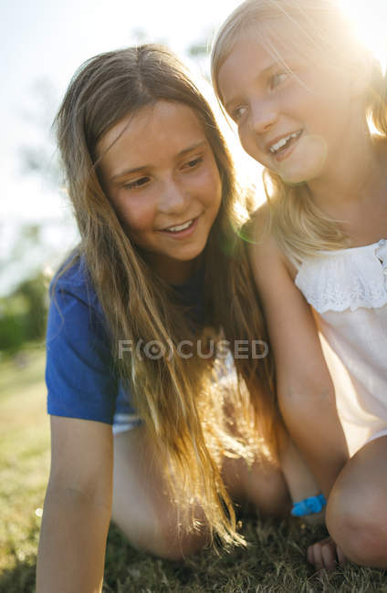 Elementary age sisters crouching side by side on meadow — Stock Photo