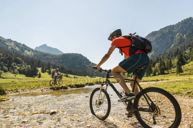 Austria, Tirolo, Valle di Tannheim, giovane in mountain bike attraversando ruscello — Foto stock