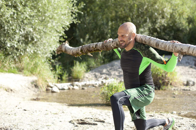 Man doing CrossFit exercise with tree trunk on his shoulders — Stock Photo