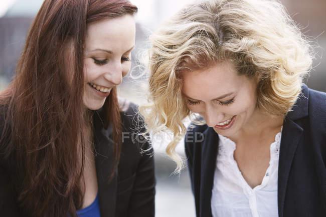 Две девушки смеются на улице — стоковое фото