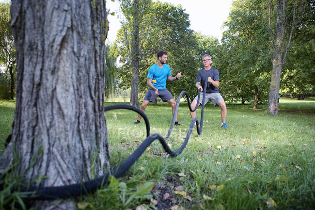 Man training with battle rope while his personal trainer watching him — Stock Photo