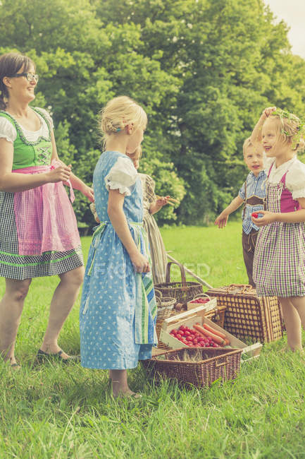 Children and teacher in traditional costumes on meadow with baskets of harvest — Stock Photo