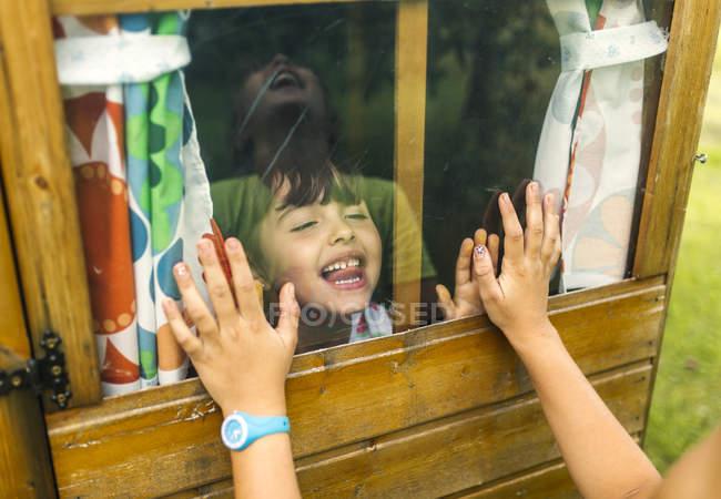 Meninas brincando através de uma janela de vidro — Fotografia de Stock