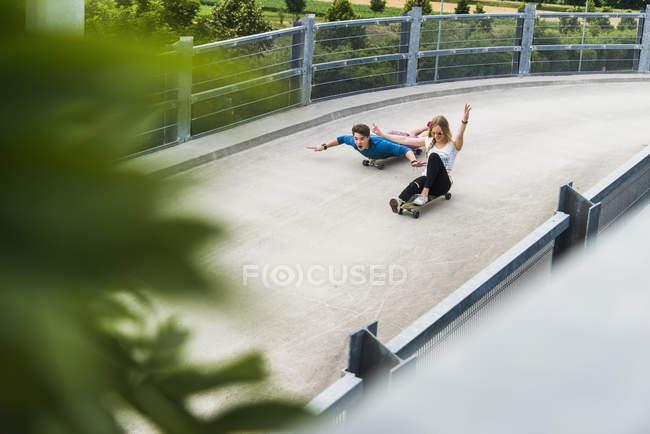 Enthousiaste jeune couple riding downhill avec planches à roulettes — Photo de stock