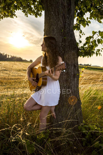 Жінка з гітарою, спираючись на стовбур дерева — стокове фото