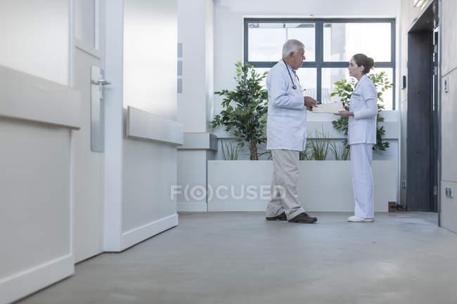 Arzt und Krankenschwester sprechen auf Krankenhausflur — Stockfoto