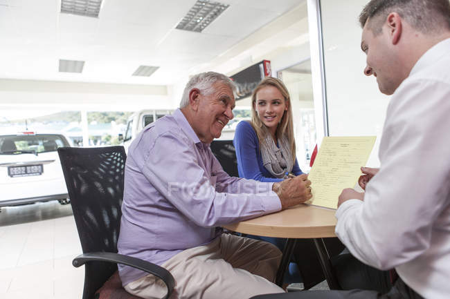 Car dealer talking to clients at table — Stock Photo