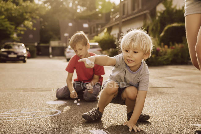Children using sidewalk chalk in their neighborhood — Stock Photo