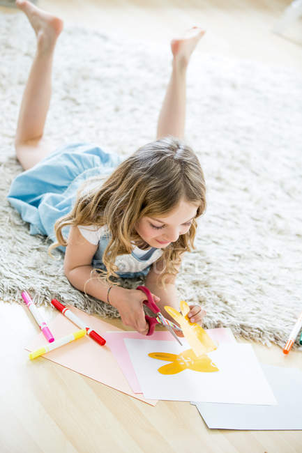 Little girl cutting out paper Easter bunnies — Stock Photo