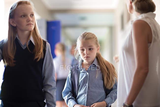 Schoolgirls with teacher walking on hallway in school — Stock Photo