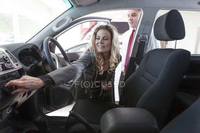 Дилер показ новий автомобіль до жінки в салоні — стокове фото
