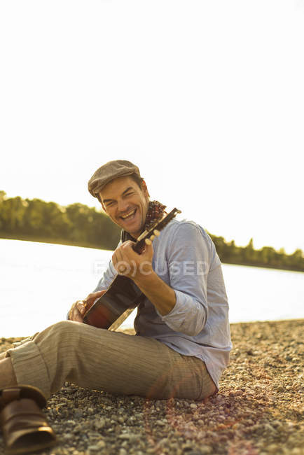 Portrait of happy man playing guitar at riverside in the evening — Stock Photo