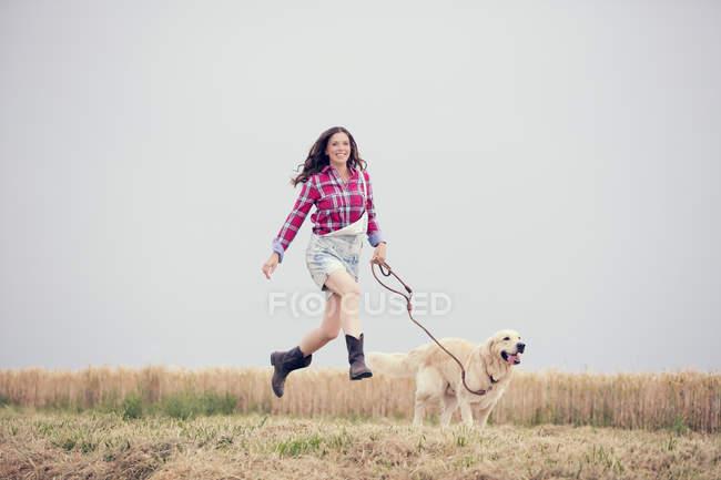 Jeune femme et son Golden Retriever à un champ — Photo de stock