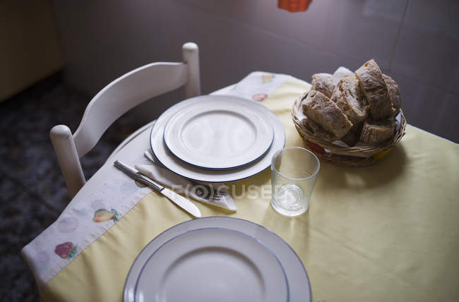 Laid table for two persons with bread basket — Stock Photo