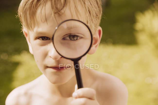 Мальчик смотрит через лупу — стоковое фото