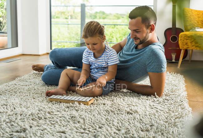 Padre con la figlia sul tappeto che gioca strumento musicale — Foto stock