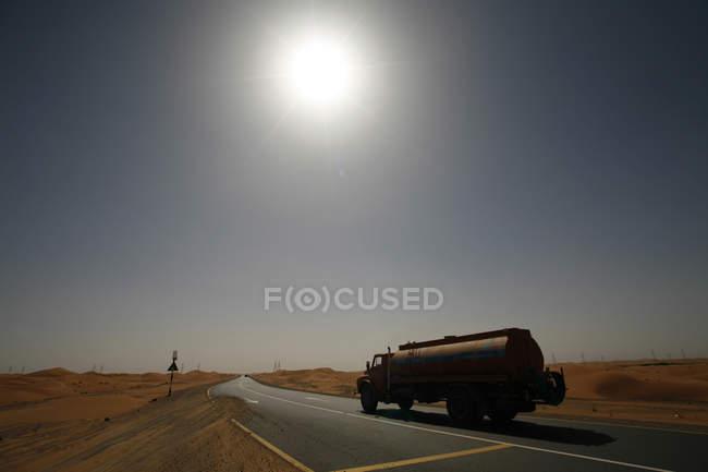 Emiratos Árabes Unidos, Abu Dhabi, desierto, camiones en carretera contra el sol - foto de stock