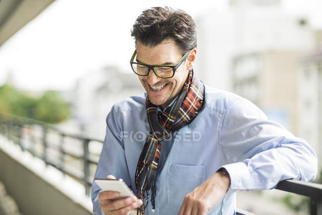 Smiling businessman looking at his smartphone — Stock Photo