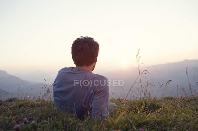 Austria, Tyrol, Unterberghorn, man resting on alpine meadow at sunset — Stock Photo