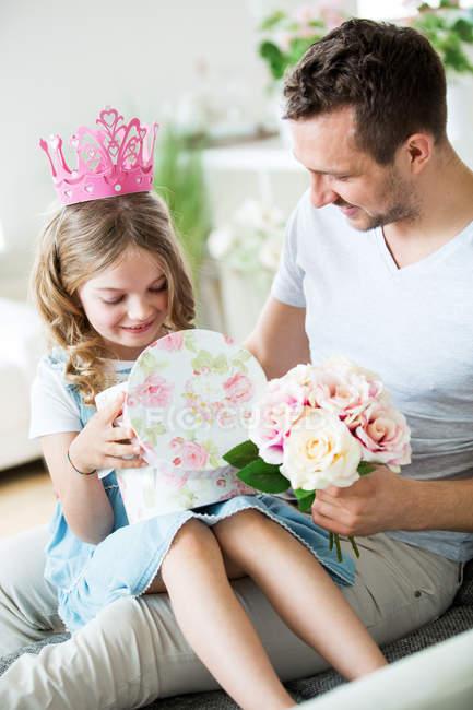 Девушка в розовой короне сидит на коленях у отца с кучей цветов — стоковое фото