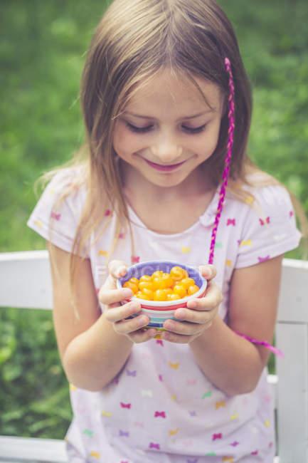 Девушка с помидорами в миске, желтые мини-помидоры — стоковое фото