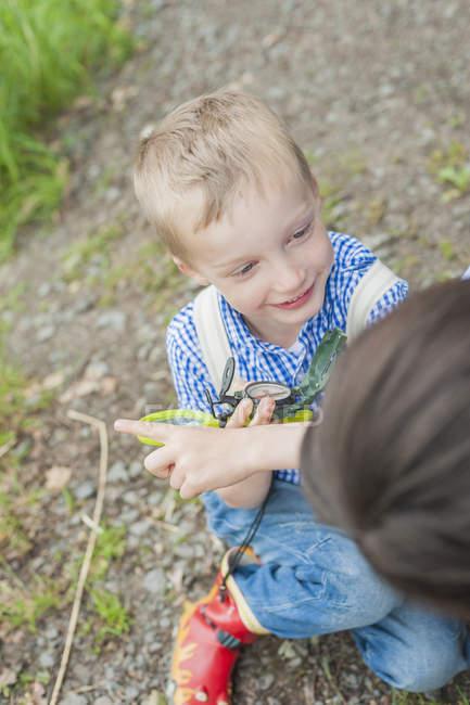 Мальчик сидит на земле и держит компас — стоковое фото