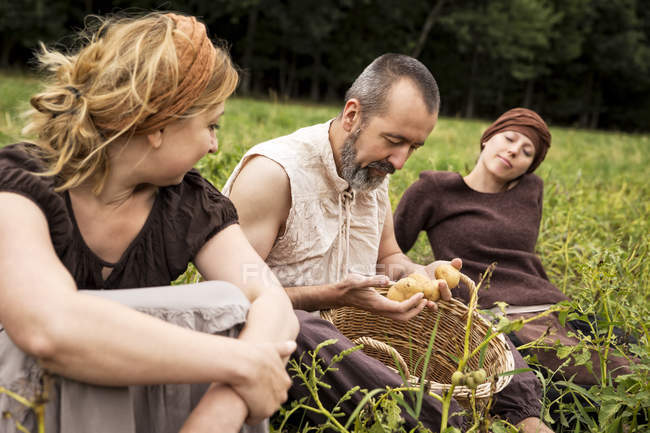 Three people sitting on field with potatoes in wicker basket — Stock Photo