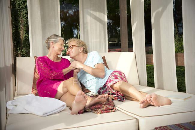 Smiling senior couple lying on lounge outdoors — Stock Photo