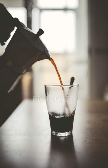 Man pouring espresso from can into a glass — Stock Photo