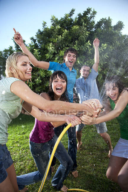 Five friends splashing with water in garden at daytime — Stock Photo