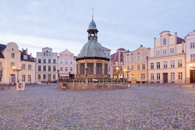 Germany, Wismar, market square with Wasserkunst at twilight — Stock Photo
