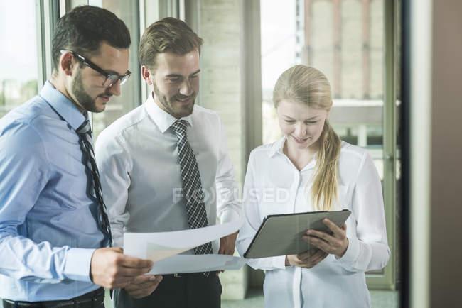 Tre giovani imprenditori in piedi con documenti e tablet digitale — Foto stock