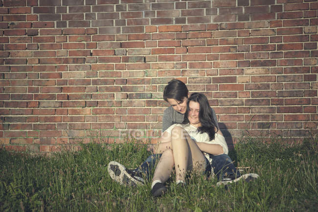 Teenage couple sitting on a meadow in front of a brick wall — Stock Photo