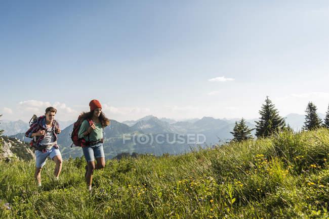Austria, Tirolo, Tannheimer Tal, coppia di giovani escursionisti sul prato alpino — Foto stock