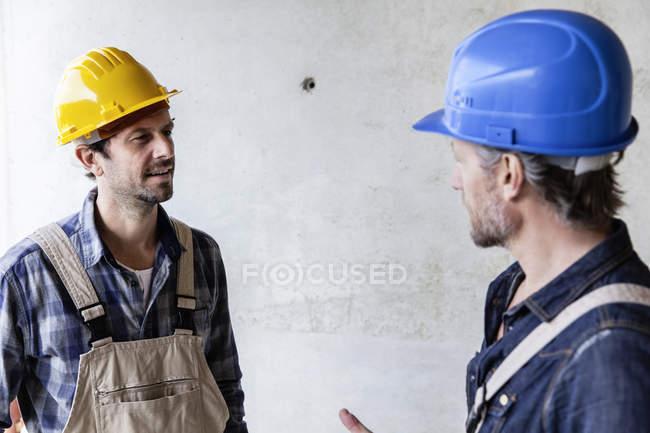 Два будівельників на будівництві сайт говорити — стокове фото