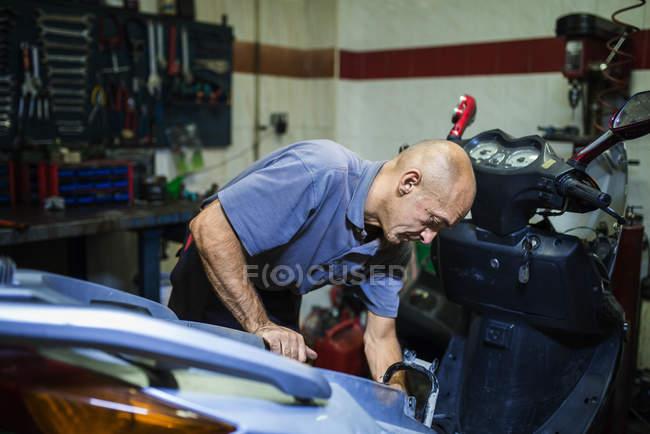Mechanic working in motor scooter workshop — Stock Photo