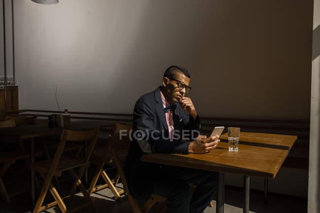 Jeune homme assis dans un café, attendant quelqu'un, lisant un message texte — Photo de stock