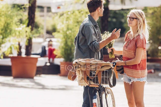 Couple with bicycle talking on street — Stock Photo